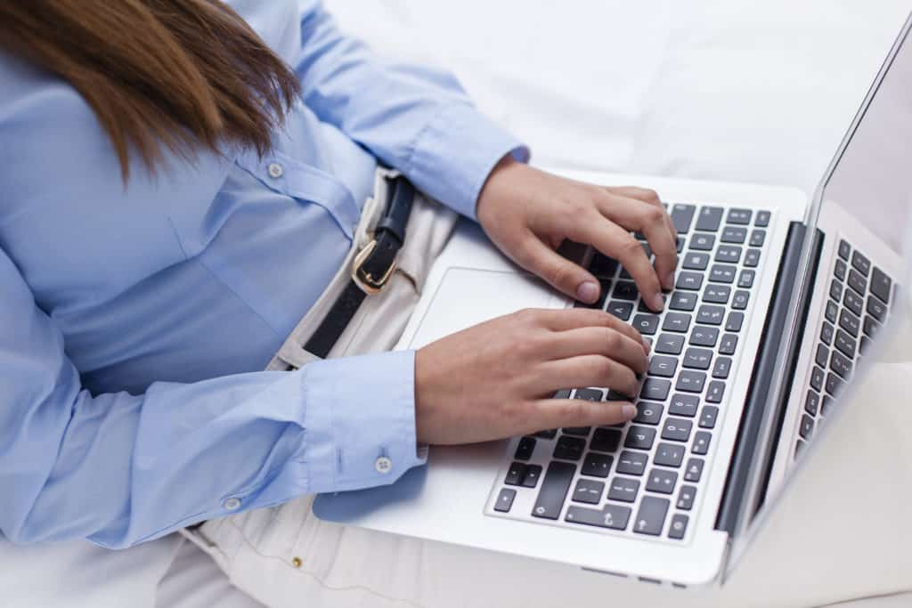 a lady typing an email on her laptop.